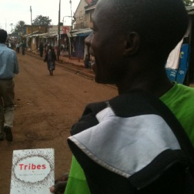 "Alex Sungubi is one of the founding members of the Blue Sweater Book Club in Nairobi. Here he's walking through Kibera with a copy of Seth Godin's ""Tribes""."