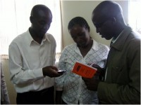"Microfinance Loan Officer Nathan Ng'etich and Regional Manager Fred Koskei show a client (center) her ""digital passbook"" via SimpleMFI on the IDEOS phone compared to her personal paper Juhudi passbook in Litein (Western Kenya)."