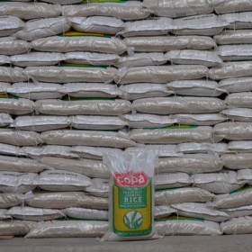 Stacks of GADCO-produced rice packaged under their Copa brand.