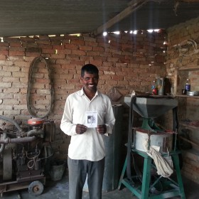 A Drishtee customer proudly displays his loan certificate.