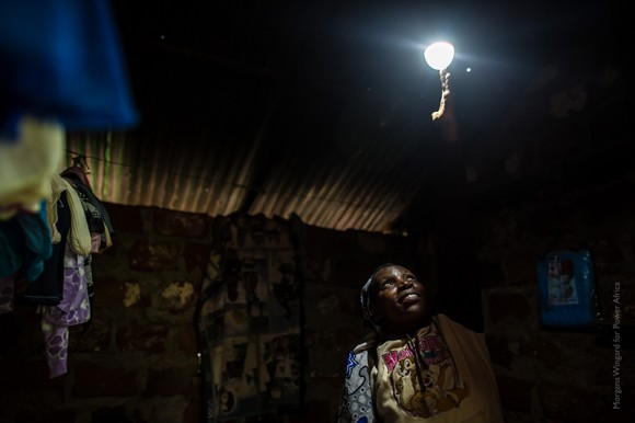 MURANG'A, KENYA: June 1, 2015 - Nancy Wambui, 45, saved for 3 months to buy d.light solar home system, a personal power grid, for her home with the help of her local village women's group. Before the d.light system her husband, Charles Macharia, 51, and her used kerosene lamps which were costly to fuel and painful to their eyes. The first night they had it, their daughter, Paris (17), stayed up until 1am studying. Before she was number 6 in class and now she is number 2. Photo by Morgana Wingard