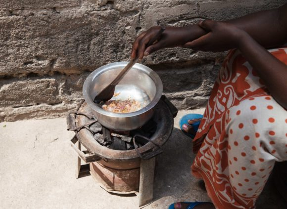 A woman in Tanzania cooks a meal for her household using charcoal.