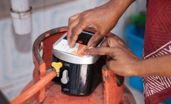 A KopaGas sales agent helps a customer with her Liquified Petroleum Gas (LPG) canister.